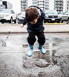 Boy jumping in a rain puddle